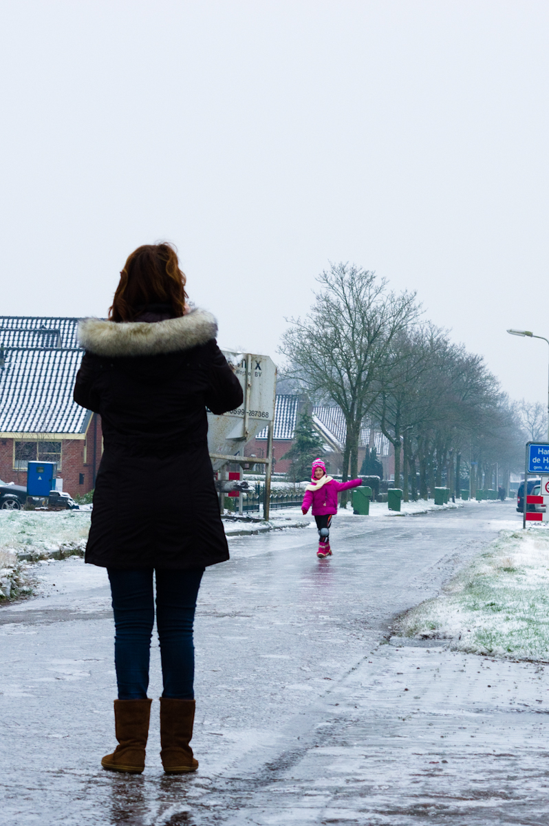 roze gekleed meisje schaats op de straten van harkema, gefotografeerd door haar moeder en door jeffrey wakanno. De ijzel hield het noorden van nederland in zijn ijzige greep.
