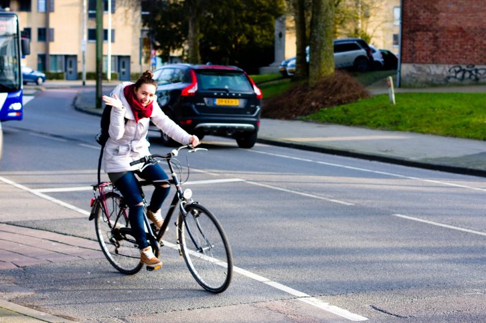 blij zwaaiend meisje te fiets in leeuwarden door jeffrey wakanno